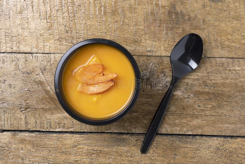 Sopa fervida da abóbora no recipiente de alimento com colher preta, refeição pronta a comer imagem de stock royalty free