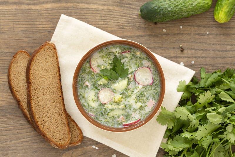 Sopa fría del yogur del verano con el rábano, el pepino, y el eneldo en la tabla de madera Sopa de verduras fría rusa en el yogur foto de archivo