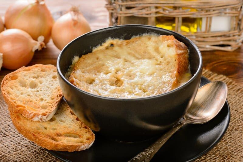 Sopa francesa da cebola com brindes na tabela de madeira fotos de stock royalty free