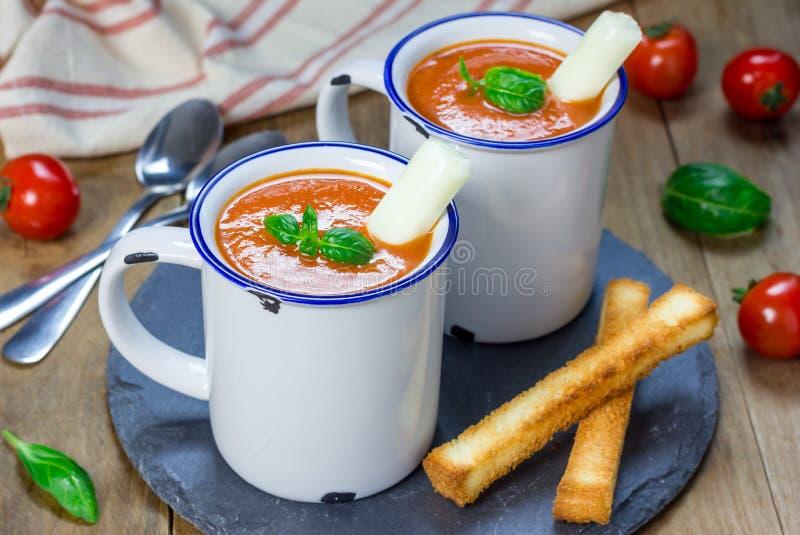 Sopa hecha en casa de la albahaca del tomate en la taza, servida con el palillo del queso de la mozzarella fotos de archivo
