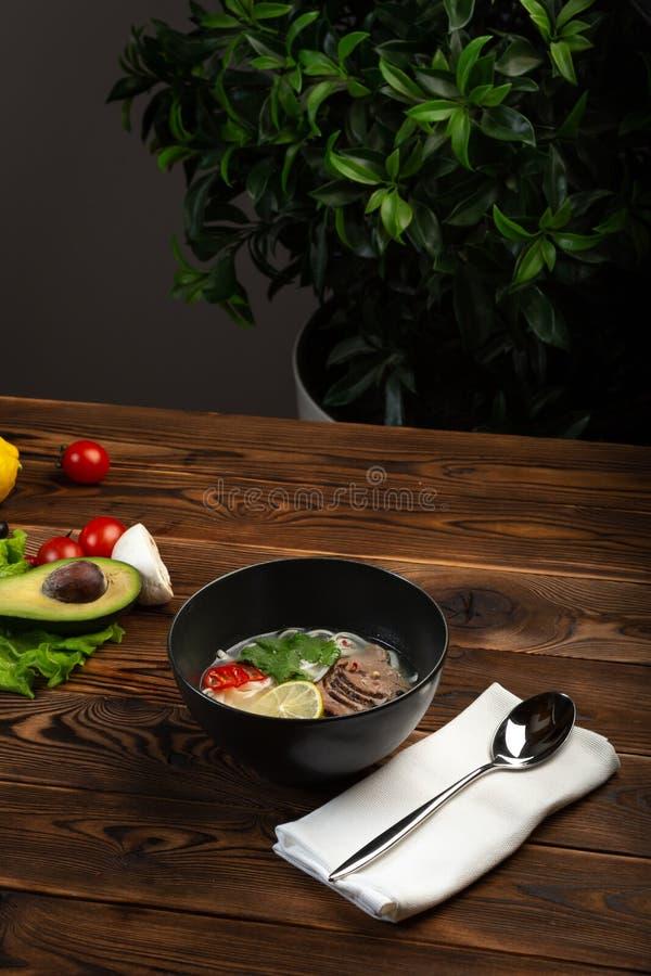 Sopa japonesa de BO del pho en una placa negra en fondo de madera imagen de archivo libre de regalías