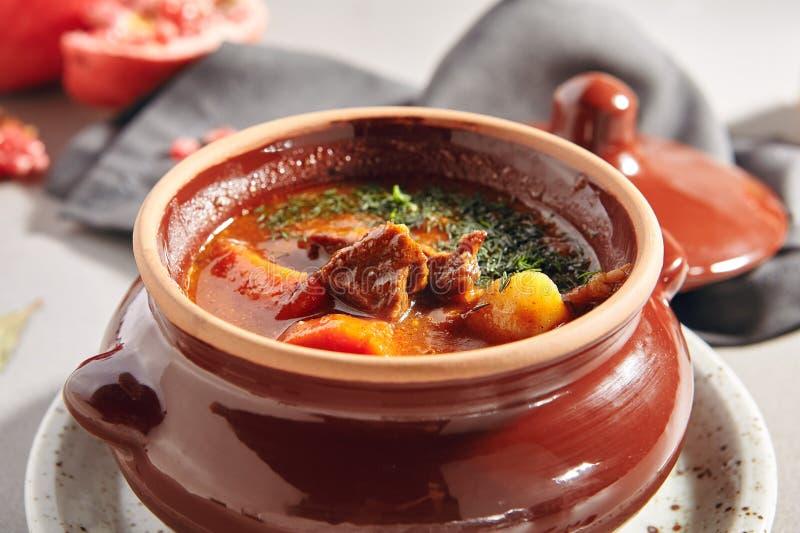 Sopa o cazuela húngara sabrosa tradicional de cocido húngaro en Cookware de cerámica foto de archivo