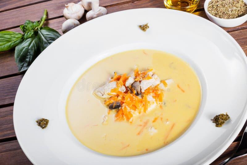 Sopa poner crema con la pechuga de pollo, setas, hierbas en la placa en fondo de madera oscuro imagenes de archivo