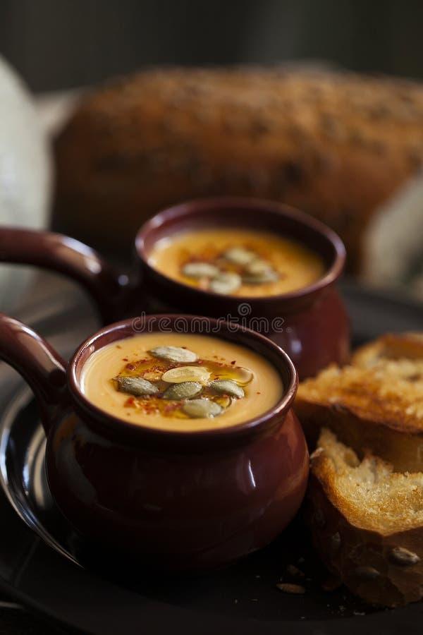 Sopa poner crema de la calabaza asada con las semillas de calabaza y los cuscurrones para Halloween Comida oscura y cambiante fotografía de archivo