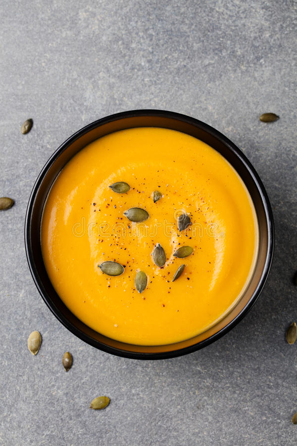Sopa poner crema de la calabaza con las semillas de calabaza en un cuenco negro Fondo de piedra gris Visión superior imagen de archivo libre de regalías