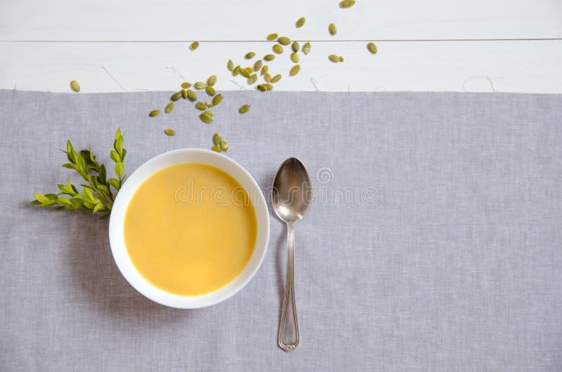 Sopa poner crema de la calabaza con las semillas de calabaza en las placas blancas con una cuchara de plata en una servilleta de  imagen de archivo libre de regalías