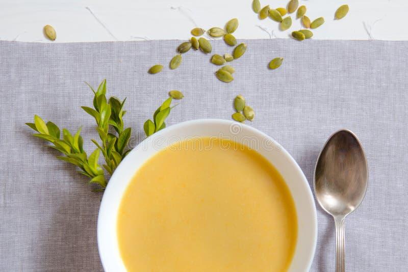 Sopa poner crema de la calabaza con las semillas de calabaza en las placas blancas con una cuchara de plata en una servilleta de  imágenes de archivo libres de regalías