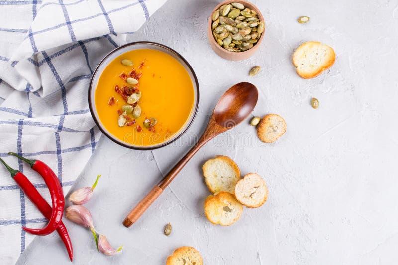 Sopa poner crema de la calabaza con las semillas, la tostada y el condimento en un cuenco de cerámica en una tabla fotos de archivo