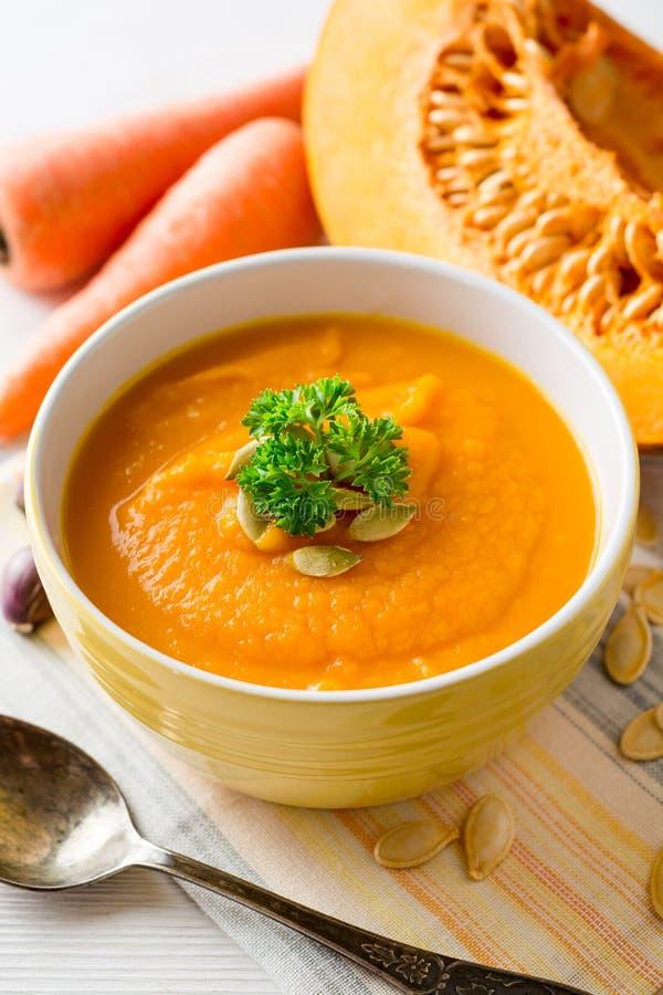 Sopa poner crema de la calabaza y de la zanahoria con las semillas y el perejil de calabaza en cuenco en el fondo de madera blanc imágenes de archivo libres de regalías