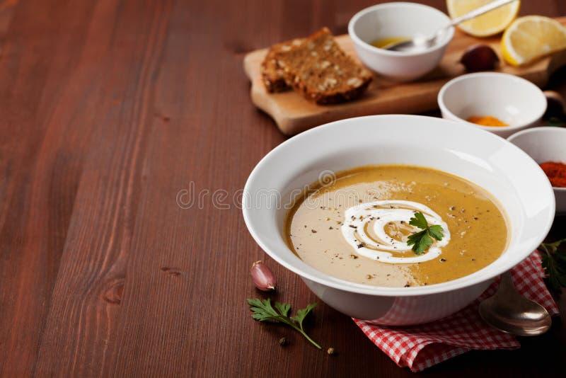 Sopa poner crema de la lenteja en un cuenco con las especias cúrcuma, paprika y ajo fotografía de archivo