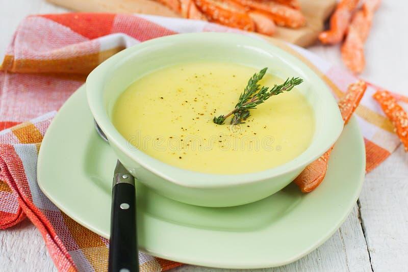 Sopa poner crema de la patata y del ajo con las barras de pan imagen de archivo