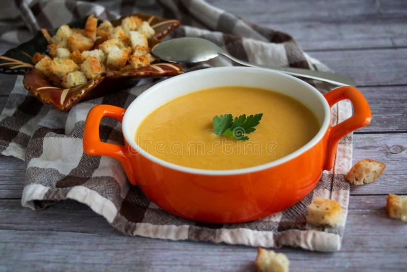 Sopa poner crema de la zanahoria de la calabaza en una placa anaranjada con las galletas en un mantel comprobado con el fondo de  imagen de archivo