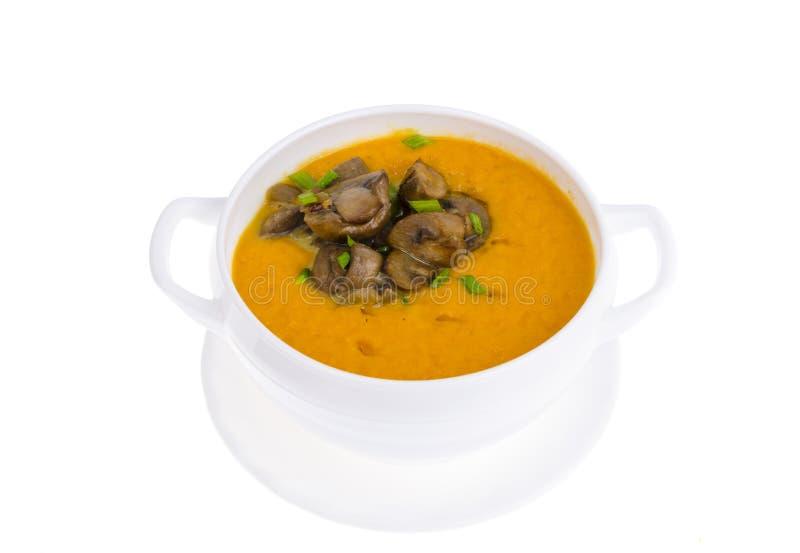 Sopa poner crema vegetal amarilla con los champiñones fritos en el cuenco blanco, aislado fotos de archivo