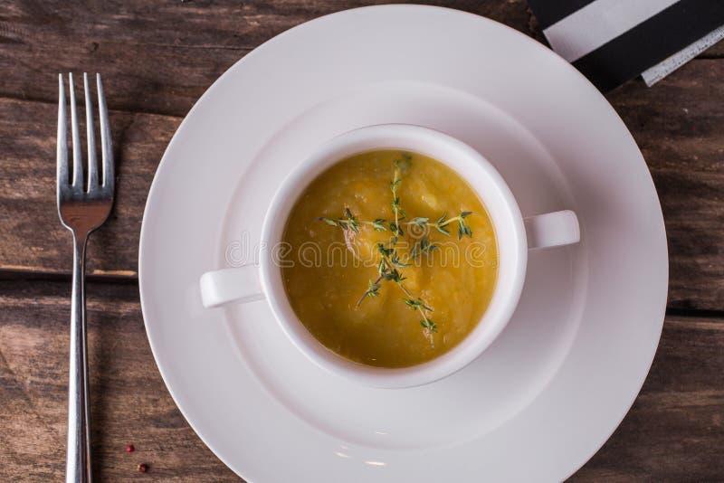 Sopa poner crema vegetal con orégano en una placa blanca imagenes de archivo