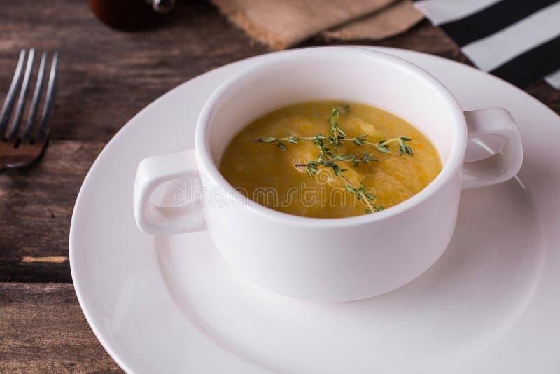Sopa poner crema vegetal con orégano en una placa blanca foto de archivo