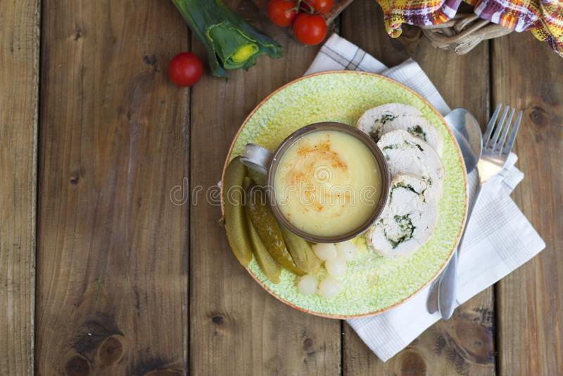 Sopa-puré en un cuenco y un rollo del prendedero del pollo en una placa del verde tomates de madera del fondo y de cereza fotos de archivo libres de regalías