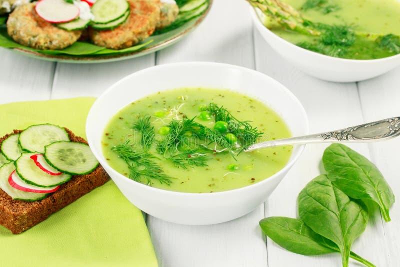 Sopa saudável do vegetariano do alimento com aspargo e espinafres, ervilhas verdes e pão com vegetais fotografia de stock royalty free
