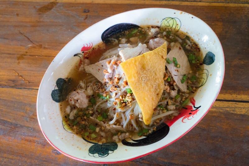 Sopa tailandesa de 'Tom Yum 'de los tallarines con cerdo y la bola de masa hervida curruscante foto de archivo libre de regalías