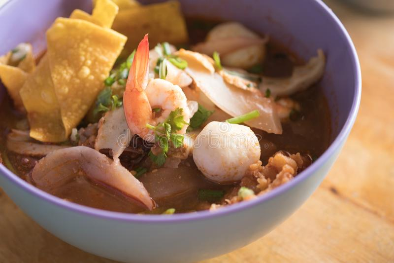 A sopa tailandesa do marisco do macarronete tem a salsa lisa da corriola dos peixes da bola da carne de porco na bacia imagem de stock royalty free