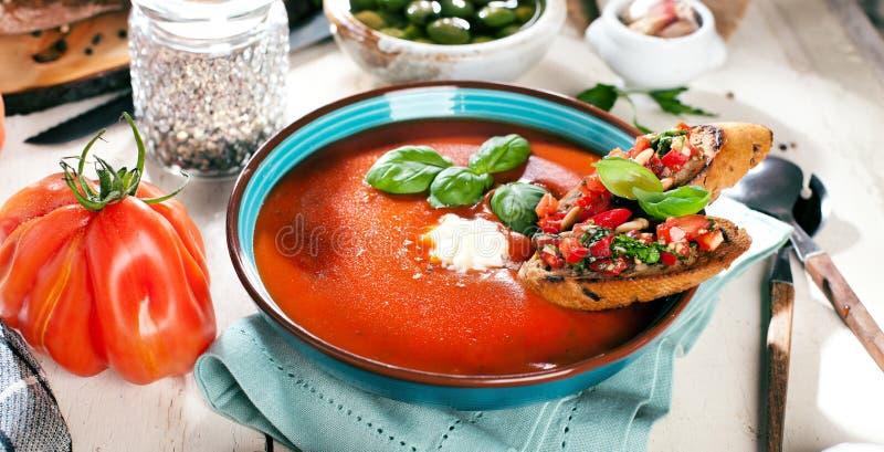 Sopa tradicional do tomate com manjericão e bruschetta fotografia de stock