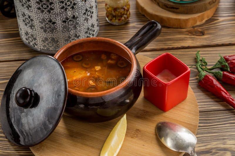 Sopa tradicional solyanka do russo com carne fumado e azeitonas no potenciômetro de argila na tabela de madeira imagens de stock