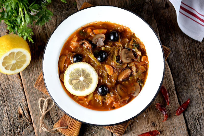 Sopa tradicional solyanka do russo feito dos cogumelos da couve, os frescos e secada com azeitonas, limão e alcaparras fotos de stock