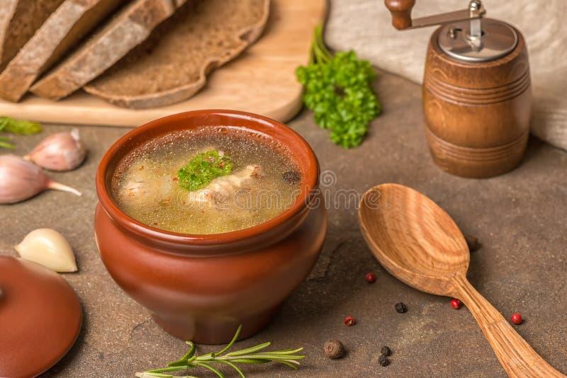 Sopa transparente de los pescados con el esturión, patatas en el pote de arcilla, decoración fotos de archivo libres de regalías