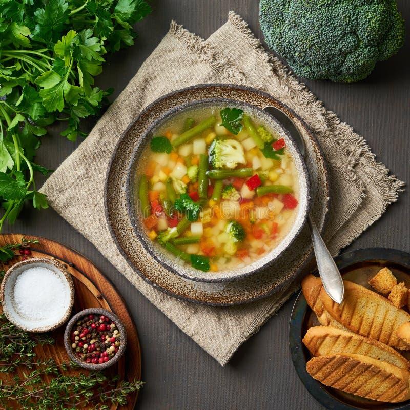 Sopa vegetal, prato brilhante da mola do vegetariano diet?tico, guardanapo de linho, vista superior, fundo escuro marrom fotografia de stock royalty free