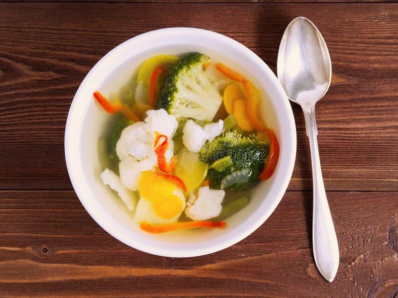 Sopa vegetariana dietética brillante con la coliflor, el bróculi y la otra verdura en el fondo de madera marrón, visión superior fotos de archivo