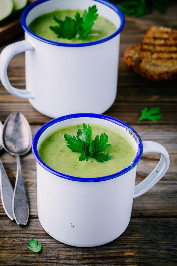 Sopa verde hecha en casa de la crema del bróculi con perejil en tazas imagen de archivo libre de regalías