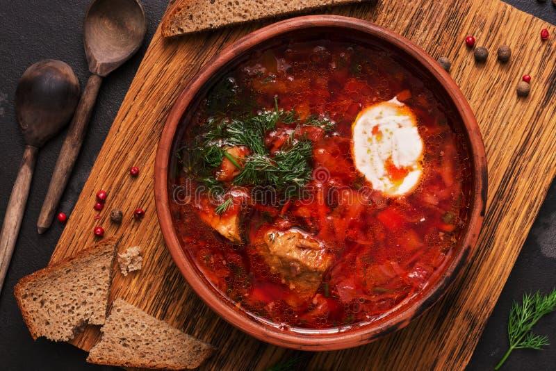Sopa vermelha do borscht ucraniano tradicional do russo com pão de centeio em um fundo escuro Borsch com carne, creme de leite e  fotos de stock royalty free