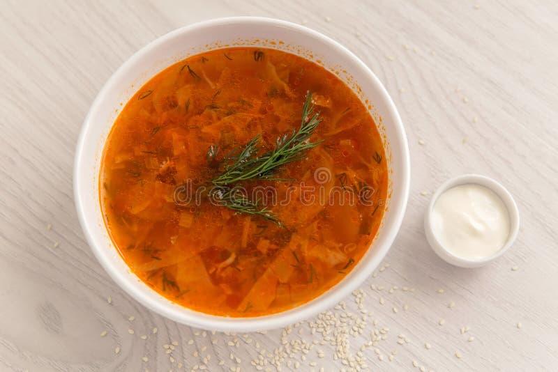 Sopa vermelha na placa branca na tabela com creme de leite fotografia de stock