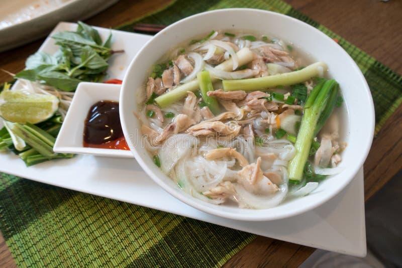 Sopa vietnamita del pho, una comida étnica de la sopa de pollo, caldo, brotes de haba, tallarines y albahaca o cilantro flotando  foto de archivo libre de regalías