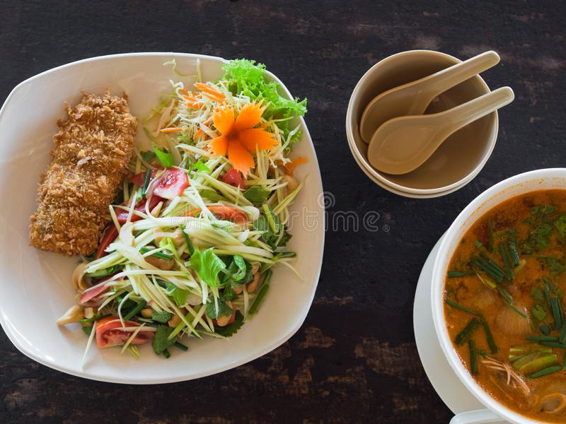 Sopa y ensalada amargas y picantes de Tom Yum Goong con el mango verde y los pescados empanados en la placa en una tabla en un re fotos de archivo