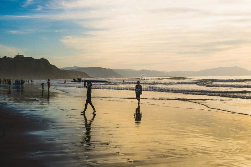 Sopelana Beach, Spain - August 16 2019: Surfers walking on the beach. Beautiful sunset in Basque Country, north of Spain stock images