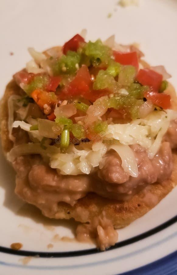 Sopes,一个传统墨西哥盘用豆,乳酪,蕃茄,在玉米粉薄烙饼的肉 库存图片