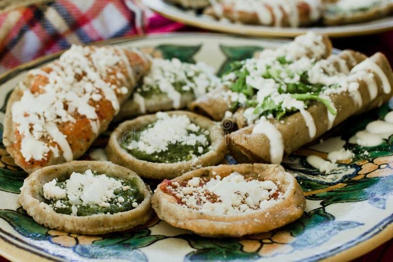 Sopes, dorados de los tacos y flautas de pollo, comida mexicana, salsa picante en México imagenes de archivo