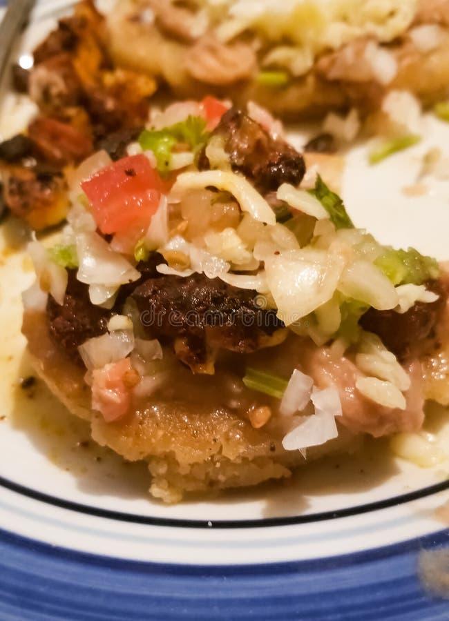 Sopes med löken, jalapeno, chili, bönor, grön sås, ost över tortillan arkivfoto