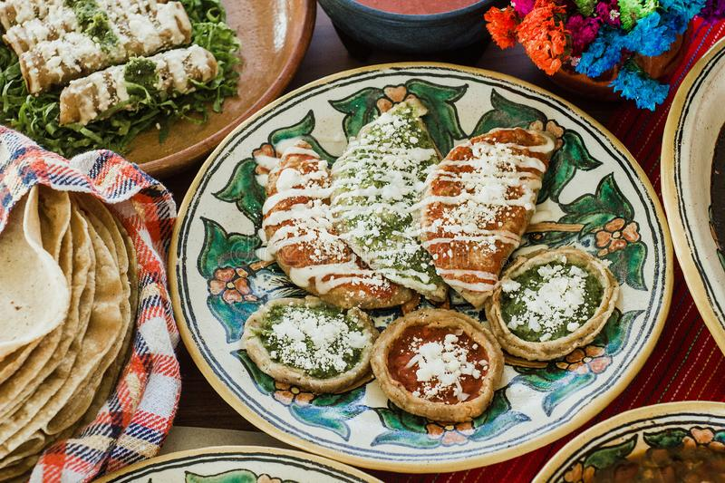Sopes, tacos dorados and flautas de pollo, Mexican food, spicy sauce in Mexico. Mexican Feast in a talavera plate stock images