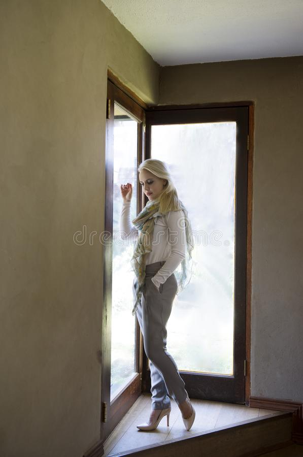 Sophisticated blonde woman wearing white shirt, grey pants,heels and scarf, posing next to glass doors with the light streaming in royalty free stock images