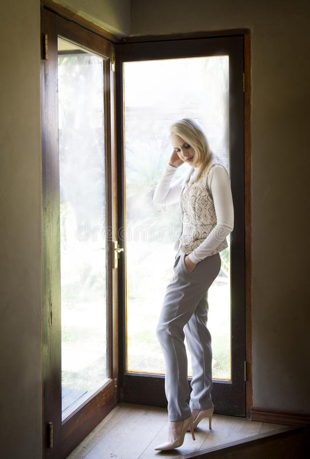 Sophisticated blonde woman wearing white shirt, grey pants,heels and scarf, posing next to glass doors with the light streaming in stock photos