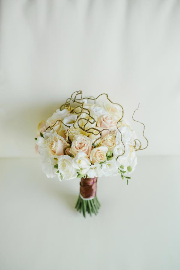 Sophisticated delicate original wedding bouquet for the bride of tea and white roses. On a light background stock images