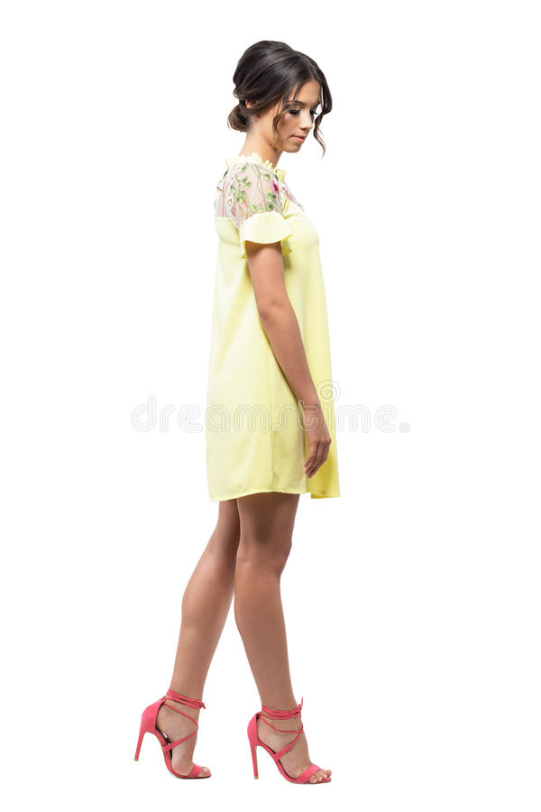 Sophisticated feminine young woman in short yellow evening dress walking and looking down stock images
