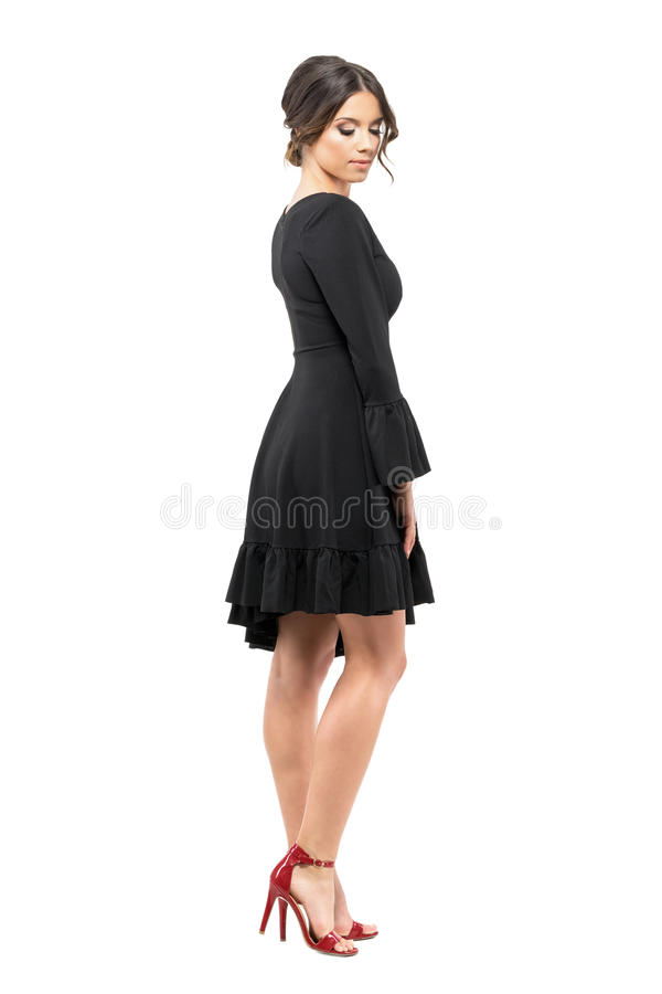 Sophisticated glamorous woman in black dress looking down. Side view. stock photo