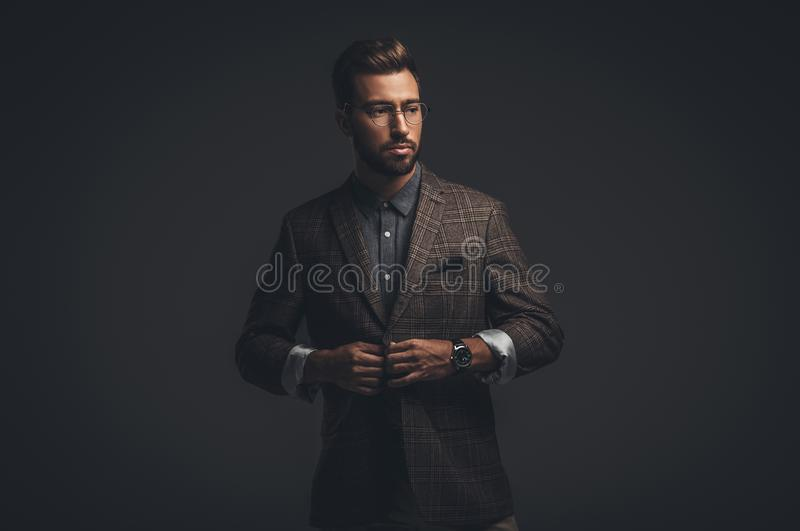 Sophisticated handsome man in suit and glasses adjusting his jacket,. Isolated on black royalty free stock image