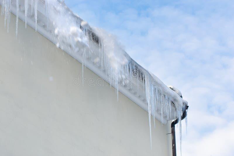 Sople i śnieg spada od dachu niebezpieczeństwo sezonu zima Niebieskie niebo z chmurami na tle zdjęcie stock