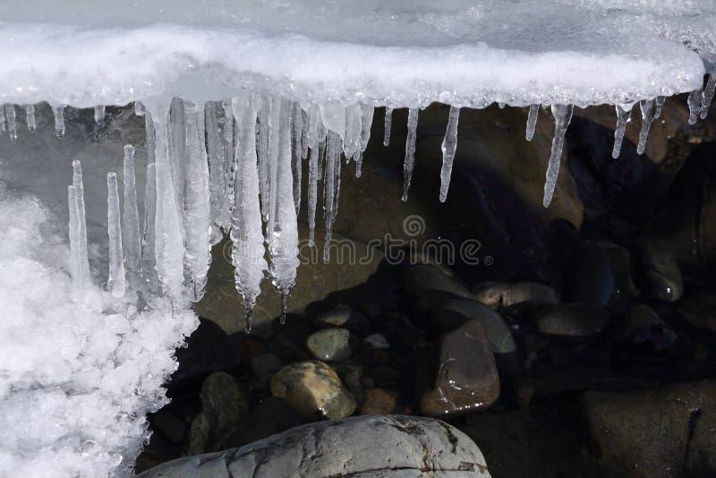 Sople na kamieniach przy odmrażanie rzeką obraz stock