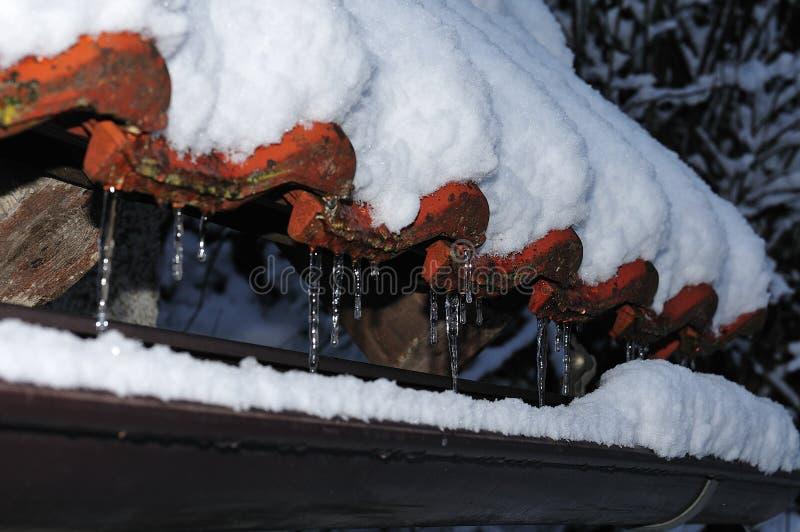 Sople przy śnieg zakrywającym dachem zdjęcia stock