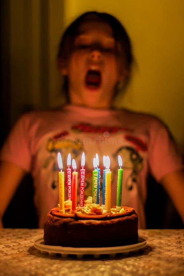 Soplo del niño en velas del cumpleaños foto de archivo