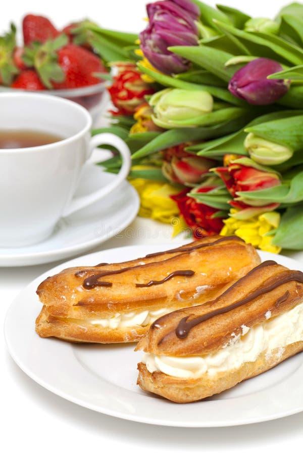 Soplo poner crema, fresa y taza frescos de té imágenes de archivo libres de regalías